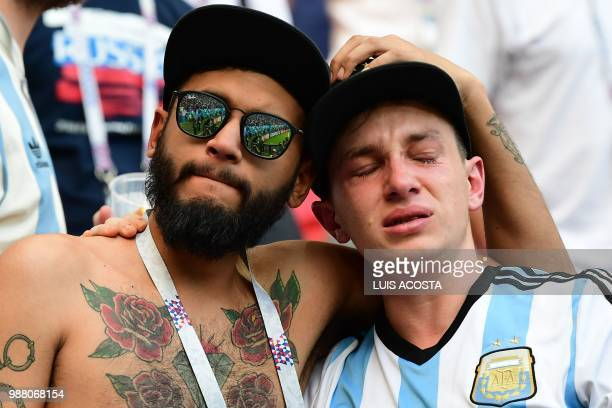 TOPSHOT Argentina fans react to their team's defeat after the Russia 2018 World Cup round of 16 football match between France and Argentina at the...