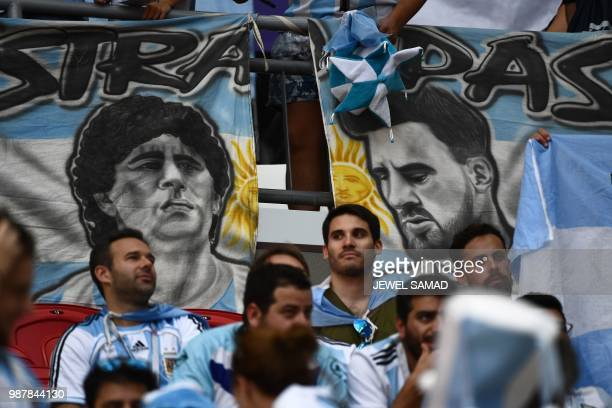 Argentina fans sit in front of banners with the images of Argentina's forward Lionel Messi and former Argentina football player Diego Maradona before...