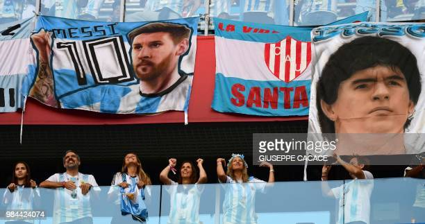 Argentina fans stand under a posters the first bearing the picture of Argentina's forward Lionel Messi and the second bearing the portrait of retired...