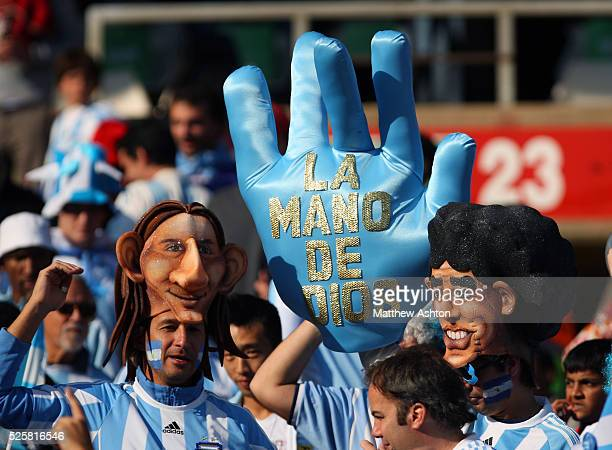 Argentina fans wearing masks of Lionel Messi and Diego Maradon hold up a giant hand with the words the hand of god in Spanish