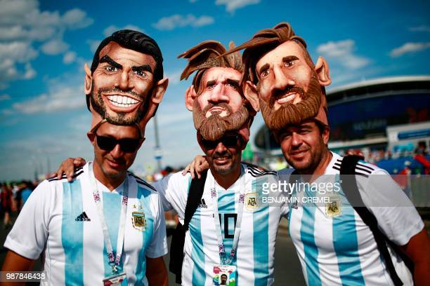 TOPSHOT Argentina fans wearing masks representing Argentina's forward Lionel Messi and Argentina's forward Sergio Aguero pose before the Russia 2018...
