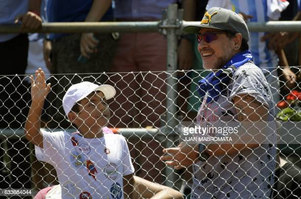 Argentina former footballer Diego Maradona gestures next to his grandson Benjamin Aguero after Italy's tennis player Paolo Lorenzi defeated by 63 63...