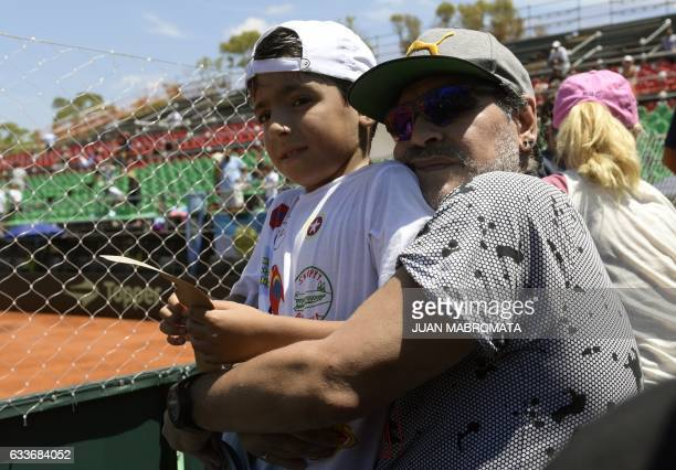 Argentina former footballer Diego Maradona poses with his grandson Benjamin Aguero after Italy's tennis player Paolo Lorenzi defeated by 63 63 63...