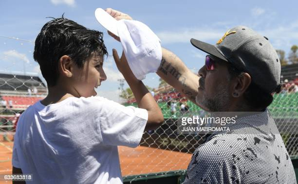 Argentina former footballer Diego Maradona straightens the cap his grandson Benjamin Aguero after Italy's tennis player Paolo Lorenzi defeated by 63...