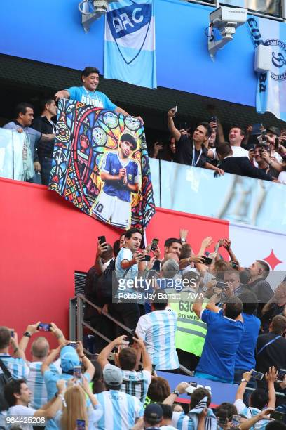 Argentina legend Diego Maradona holds a flag of himself as fans react prior to the 2018 FIFA World Cup Russia group D match between Nigeria and...