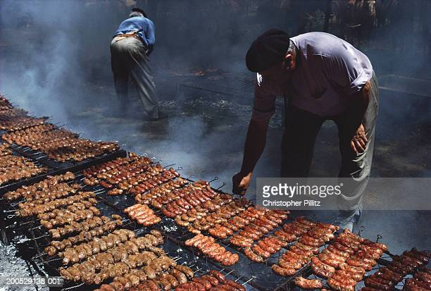 Argentina, man turning sausages on large barbecue.
