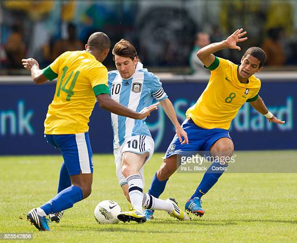 Argentina National Team Captain Lionel Messi works the ball through Brazil National Team players Romulo and Juan during the Clash of the Titans match...
