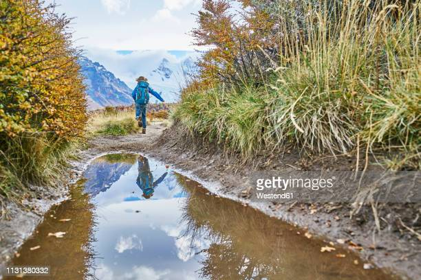 argentina, patagonia, el chalten, boy running at puddle at cerro torre in los glaciares national park - cerro torre stock-fotos und bilder