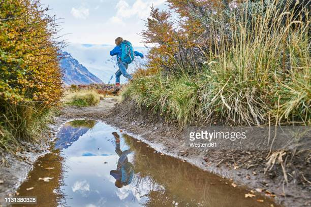 argentina, patagonia, el chalten, boy running at puddle in los glaciares national park - chalten stock pictures, royalty-free photos & images