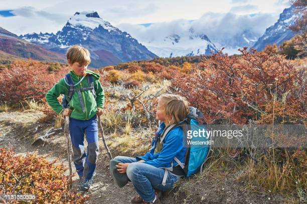 argentina, patagonia, el chalten, two boys having a break from hiking in los glaciares national park - chalten stock pictures, royalty-free photos & images