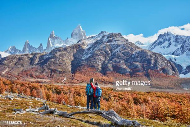 argentina, patagonia, el chalten, two boys on a hiking trip embracing at fitz roy massif - santa cruz province argentina stock pictures, royalty-free photos & images