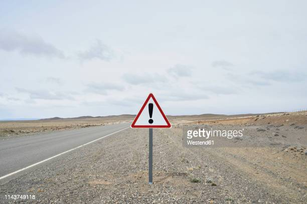 argentina, patagonia, empty road with exclamation mark sign in the middle of desert - the hobbit: an unexpected journey stock pictures, royalty-free photos & images