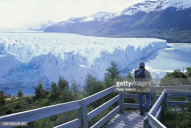 Argentina, Patagonia, man on walkway overlooking glacier, rear view