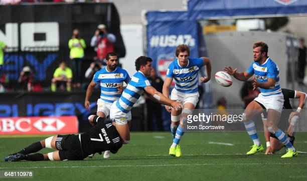 Argentina player Joaquin Riera left passes to Fernando Luna while being tackled by New Zealand player Iopu IopuAso during their sevens rugby match...