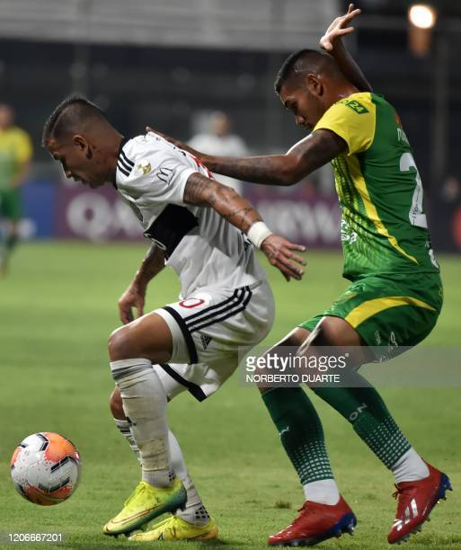 Argentina 's Defensa y Justicia player Francisco Pizzini vies for the ball with Paraguay's Olimpia player Derlis Gonzalez during their Copa...