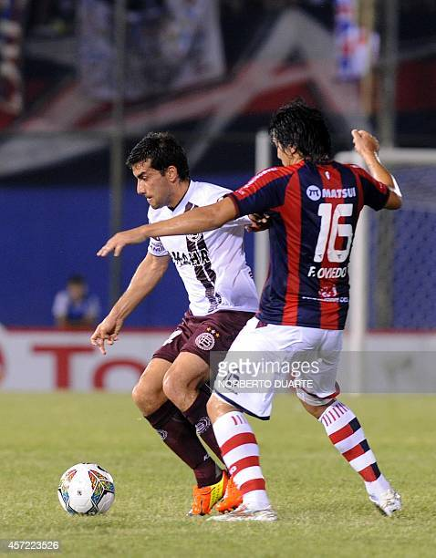 Argentina 's Lanus' Carlos Araujo vies for the ball with Fidencio Oviedo of Paraguay's Cerro Porteno during their Copa Sudamercana football match at...