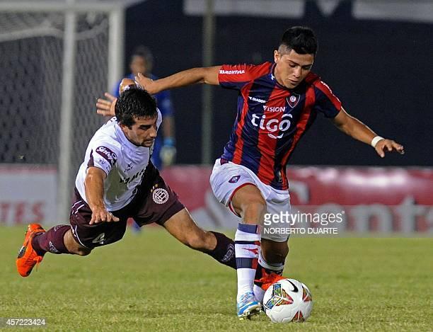 Argentina 's Lanus4 Carlos Araujo vies for the ball with Jose Ortigoza of Paraguay's Cerro Porteno during their Copa Sudamercana football match at...