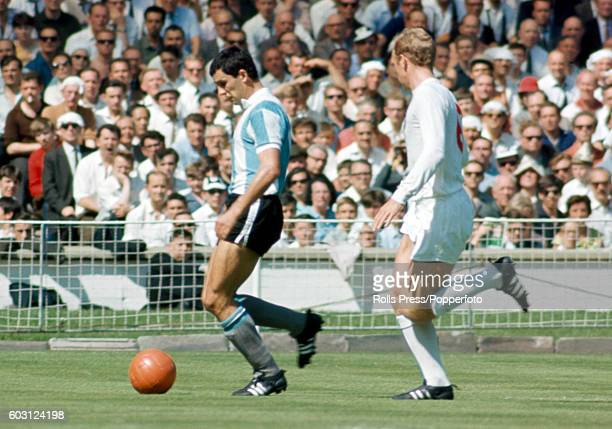 Argentina striker Luis Artime is shadowed by England captain Bobby Moore during the World Cup quarterfinal match between England and Argentina at...