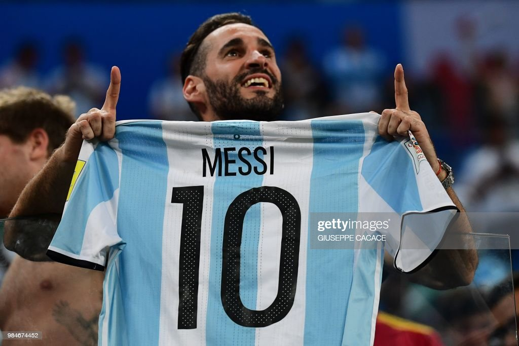 TOPSHOT - Argentina supporters carry a jersey of Argentina's forward Lionel Messi during the Russia 2018 World Cup Group D football match between Nigeria and Argentina at the Saint Petersburg Stadium in Saint Petersburg on June 26, 2018. (Photo by Giuseppe CACACE / AFP) / RESTRICTED