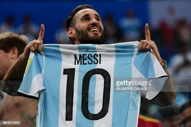TOPSHOT Argentina supporters carry a jersey of Argentina's forward Lionel Messi during the Russia 2018 World Cup Group D football match between...