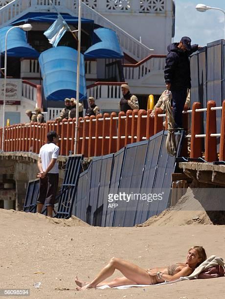 Una mujer toma sol mientras personal de la Prefectura de Mar del Plata Argentina acomoda algunas de las vallas que cierran la zona de exclusion...