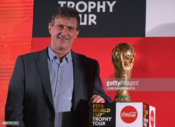 Argentina's 1978 World Cup Champion and former footballer Mario Kempes poses next to the FIFA World Cup trophy in Ezeiza Buenos Aires on March 29...