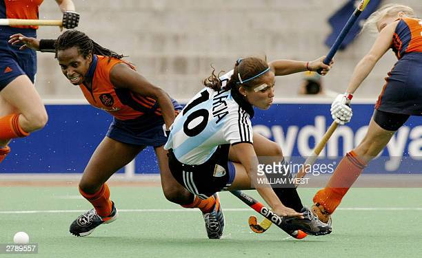 Argentina's Agustina Garcia is brought down by the Netherlands defence of Maartje Scheepstra and Janneke Schopman conceding a penalty in their...