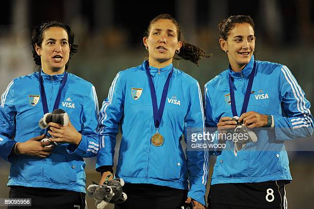 Argentina's Alejandra Gulla Soledad Garcia and Luciana Aymar sing on the victory podium after winning the gold medal match against Australia at the...