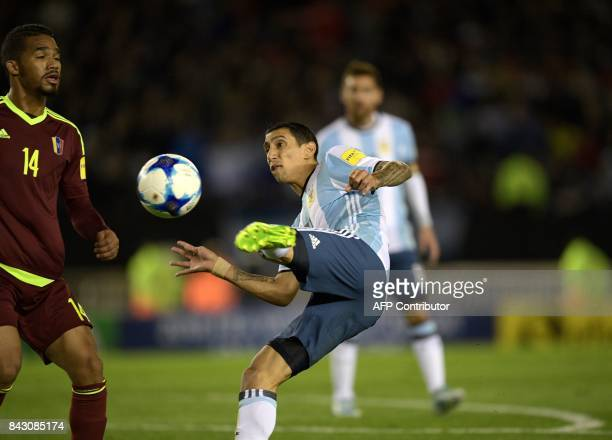 Argentina's Angel Di Maria and Venezuela's Yangel Herrera vie for the ball during their 2018 World Cup qualifier football match in Buenos Aires on...
