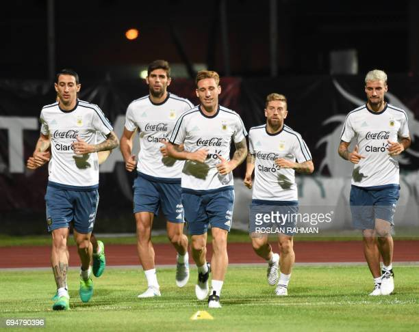 Argentina's Angel Fabian Dimaria Federico Fazio and Lucas Biglia and teammates warm up during a training session at Bishan stadium in Singapore on...