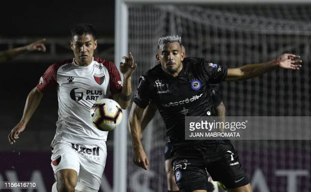 Argentina's Argentinos Jrs Victorio Ramis vies for the ball with Argentina's Colon defender Alex Vigo during their Copa Sudamericana sixteen round...