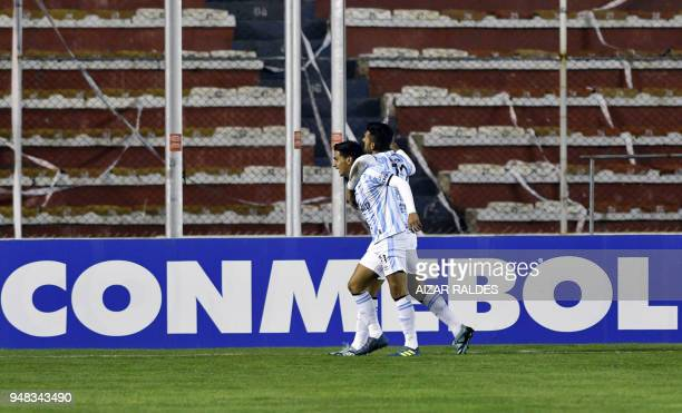 Argentina's Atletico Tucuman player Favio Enrique Alvarez celebrates with a teammate after scoring against Bolivia's The Strongest during their Copa...