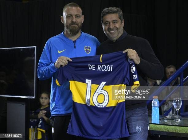 Argentina's Boca Juniors president Daniel Angelici poses with Italian midfielder Daniele De Rossi and his jersey during his presentation at the...