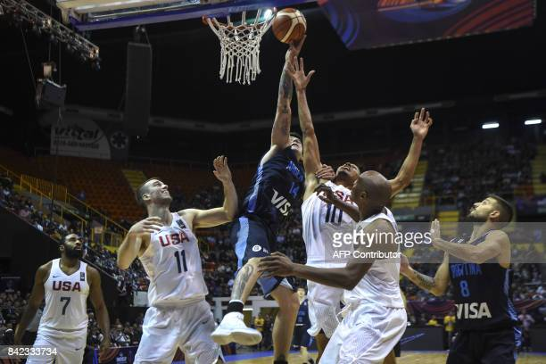 Argentina's center Gabriel Deck shoots marked by USA's center Marshall Plumpee and shooting guard Reggie Hearn during their 2017 FIBA Americas...