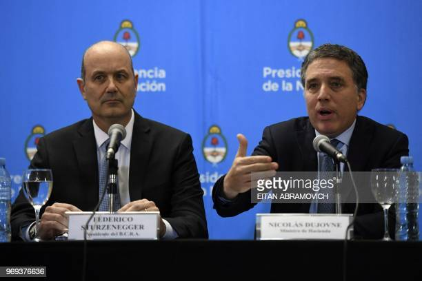 Argentina's Central Bank Governor Federico Sturzenegger listens while Argentina's Finance Minister Nicolas Dujovne speaks during a press conference...