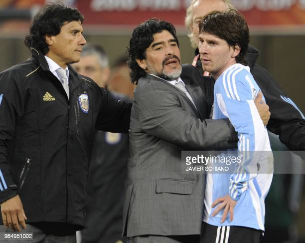 Argentina's coach Diego Maradona hugs Argentina's striker Lionel Messi after the 2010 World Cup quarter final Argentina vs Germany on July 3 2010 at...
