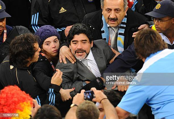 Argentina's coach Diego Maradona is accompanied by his daughter Dalma as he leaves the field after losing to Germany in a 2010 World Cup quarterfinal...