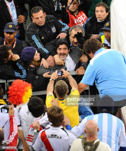 Argentina's coach Diego Maradona is accompanied by his daughter Dalma as he says some words to spectators while leaving the field after losing to...