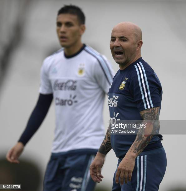 Argentina's coach Jorge Sampaoli gives instructions near midfielder Leandro Paredes during a training session in Ezeiza Buenos Aires on August 29...