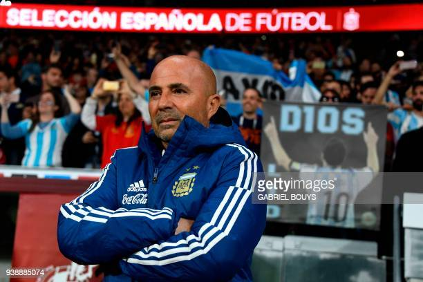 Argentina's coach Jorge Sampaoli stands in front of fans holding a picture of Argentina's forward Lionel Messi before a friendly football match...