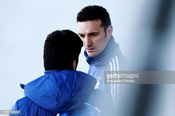 Argentina's coach Lionel Scaloni speaks to a staff member during a training session at Real Madrid's training facilities of Valdebebas in Madrid on...