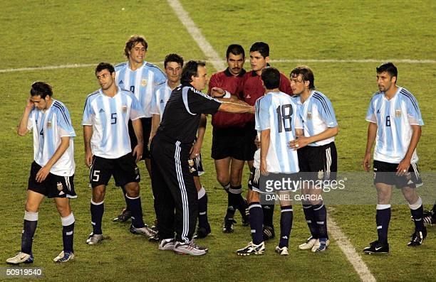 Argentina's coach Marcelo Bielsa separates his players from the referee Oscar Ruiz and the lineman at the end of the football match against Brazil at...