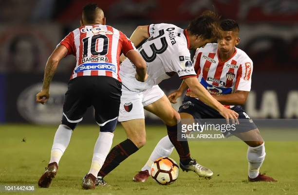 Argentina's Colon player Christian Bernardi vies for the ball with Colombia's Junior players Jarlan Barrera and David Murillo during their Copa...