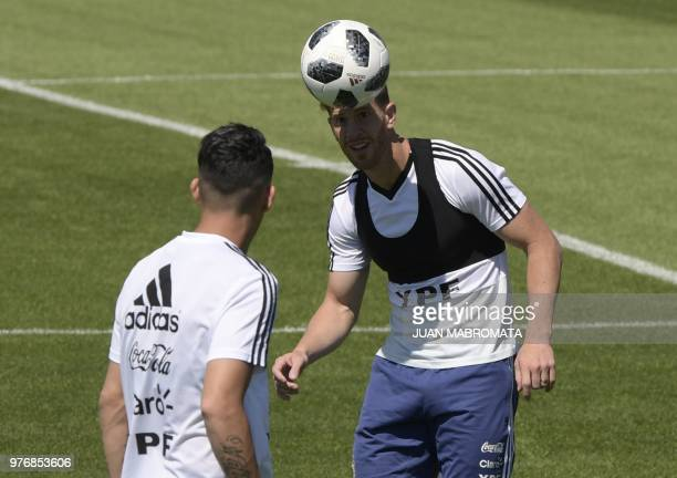 Argentina's defender Cristian Ansaldi heads the ball next to midfielder Cristian Pavon during a training session at the team's base camp in Bronnitsy...