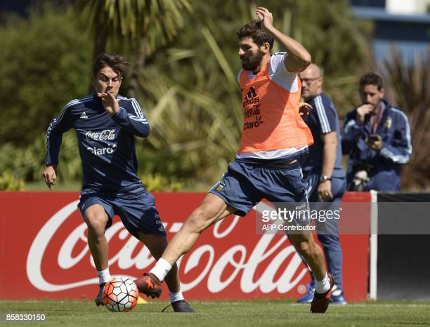 Argentina's defender Federico Fazio vies for the ball with forward Paulo Dybala during a training session in Ezeiza Buenos Aires on October 6 2017...