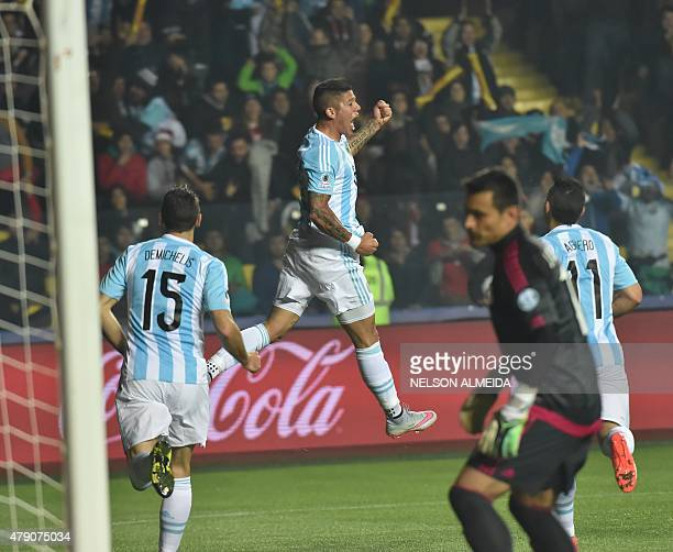 Argentina's defender Marcos Rojo celebrates after scoring against Paraguay next to teammates Argentina's defender Martin Demichelis and Argentina's...