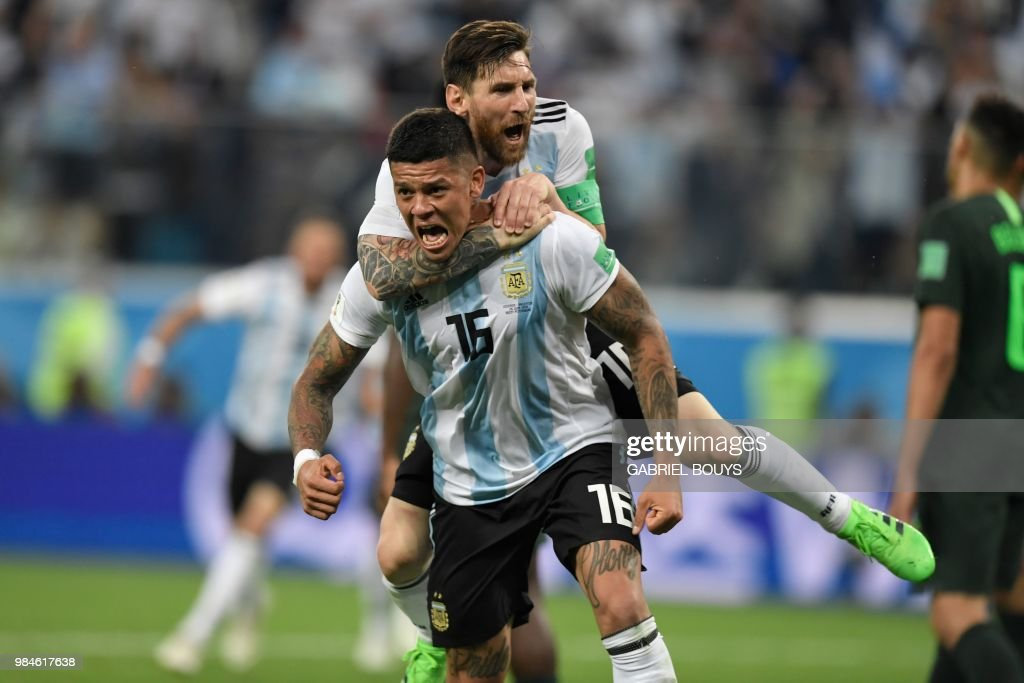 TOPSHOT - Argentina's defender Marcos Rojo (lower) celebrates his goal with Argentina's forward Lionel Messi during the Russia 2018 World Cup Group D football match between Nigeria and Argentina at the Saint Petersburg Stadium in Saint Petersburg on June 26, 2018. (Photo by GABRIEL BOUYS / AFP) / RESTRICTED