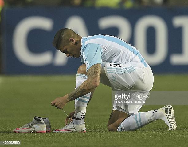 Argentina's defender Marcos Rojo changes his boots during their Copa America semifinal football match against Paraguay in Concepcion Chile on June 30...