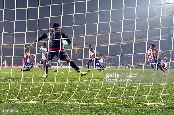 Argentina's defender Marcos Rojo kicks to score against Paraguay's goalkeeper Justo Villar during their Copa America semifinal football match in...