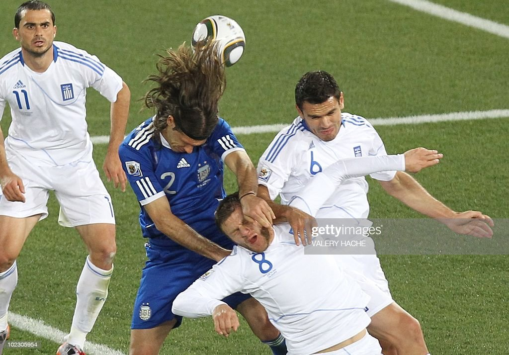 Argentina's defender Martin Demichelis (2ndL) heads the ball past Greece's defender Avraam Papadopoulos (down) and Greece's midfielder Alexandros Tziolis (R) during the Group B first round 2010 World Cup football match Greece vs Argentina on June 22, 2010 at Peter Mokaba stadium in Polokwane. NO